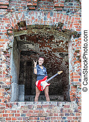 punk girl with electric guitar standing in the window