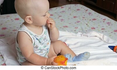 A handsome baby eating a peach on a breakfast in bed He...