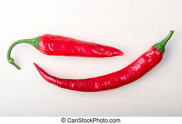 Two red hot chili peppers closeup on wooden background