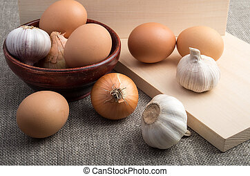 Eggs, onions and garlic next to an old wooden bowl - Still...