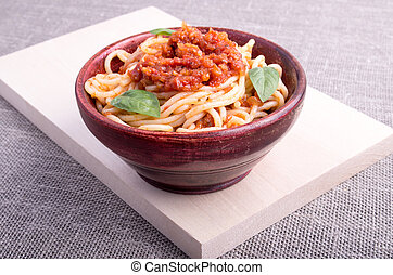 Cooked spaghetti in a brown small wooden bowl - Cooked...