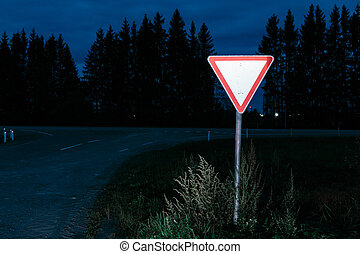 Road sign give way. Road sign at night on the background...