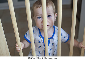 Baby boy behind the wooden safety gate of stairs - One year...