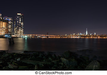 Manhattan by night with a view on the Manhattan Bridge illuminated