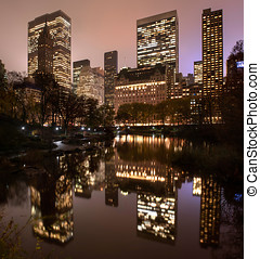 Reflections of Manhattan in Central Park pond at night