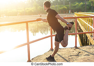 Fitness man stretching his leg before a run outdoors. -...