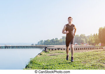 Fit man running outdoor in nature on beach Morning training....