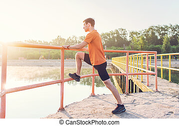 Fitness man stretching his leg muscles outdoors - Fitness...