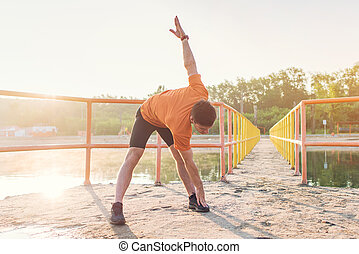 Young sporty man bending down and doing stretching exercise....