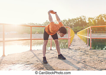 Young athlete holding his arms behind back and stretching...