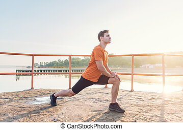 Young fit man stretching legs outdoors doing forward lunge -...