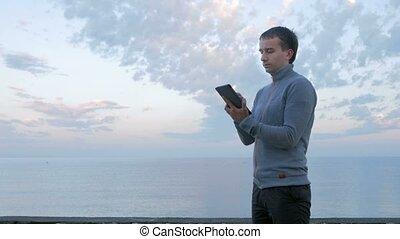 A man walks along the beach near the ocean with the tablet....