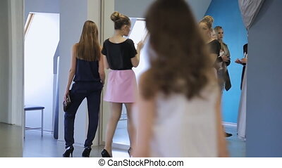 Young females are preparing for fashion show in model school.