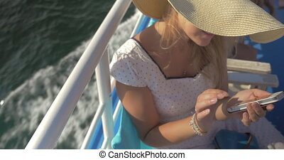 Young woman engaged in smartphone is on ship and smiling top...