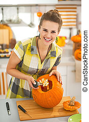 housewife prepare big orange pumpkin for Halloween party -...