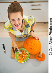 happy woman carving a big orange pumpkin Jack-O-Lantern -...