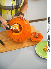Closeup on woman prepare big orange pumpkin Jack-O-Lantern -...