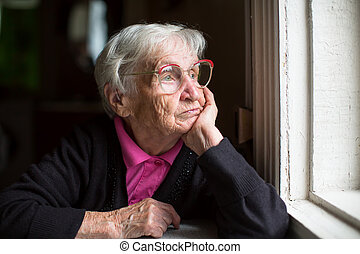 Elderly woman looking out window - Elderly woman in glasses...
