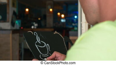 Man draws a chalk on a black board a mug of coffee. In the...