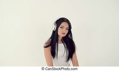 woman listening to music on headphones - brunette woman in a...
