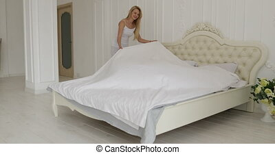 woman runs the linen on the bed man hug her couple home bedroom