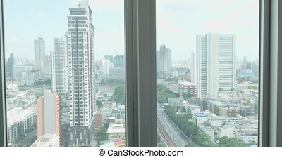 View from window of buildings and bustling road and resting...