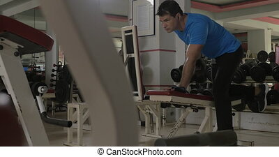 At the gym young man doing exercise for triceps