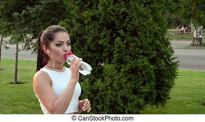 woman with headphones drinking water - sporty brunette woman...