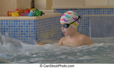 View of boy playing with toy in the kids swimming pool -...