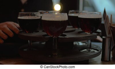 Beer glasses served on rotating tray - Woman rotating wooden...
