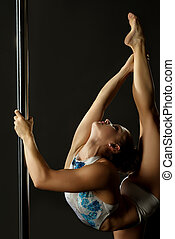 Girl performs gymnastic split while holds on pylon