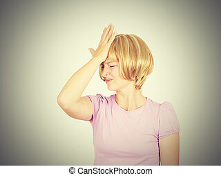 Witless young woman holding her hand to her forehead. Blonde...
