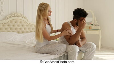 couple problem man sitting on bed unhappy woman comfort him...