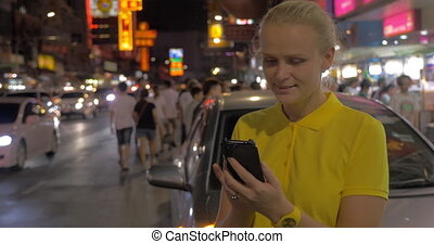 Woman texting on cell and looking at night Bangkok, Thailand...
