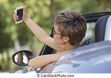 closeup of young Chinese woman taking photo in a convertible car