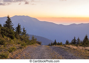 Sunset in Carpathian mountains with a gravel road in front