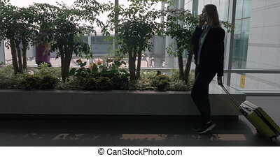 Woman talking on mobile while walking in the airport terminal