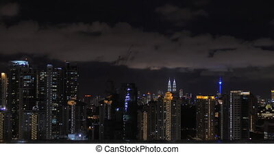 Woman looking at night Kuala Lumpur from rooftop pool -...
