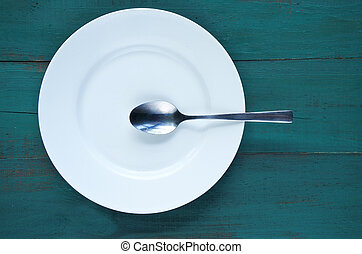 Empty plate with spoon on wooden background - White empty...