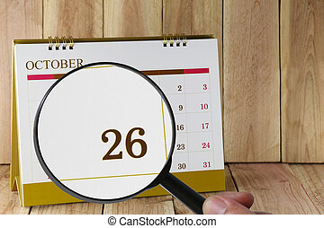 Magnifying glass in hand on calendar you can look Twenty-six...