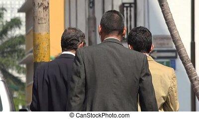 Business Men Walking On Sidewalk