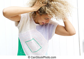 Young mixed race woman laughing with hands in curly hair