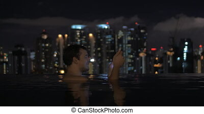 View of man in swimming pool on the skyscraper roof using tablet against night city landscape.