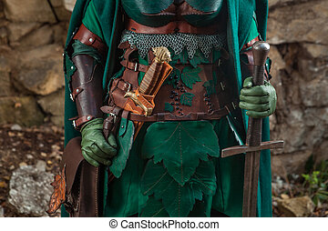 Close up of elf's leather armor, sword and dagger
