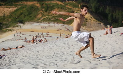 Young man dancing on beach