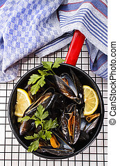 boiled mussels with lemon and parsley in an enamel pot -...