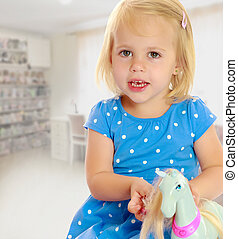 Girl playing with horse - Cute little blonde girl playing...