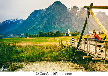 Tourist relaxing on bridge in village Oppstryn Norway -...