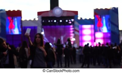 Blurred girl making selfie with her phone. Outdoor live...