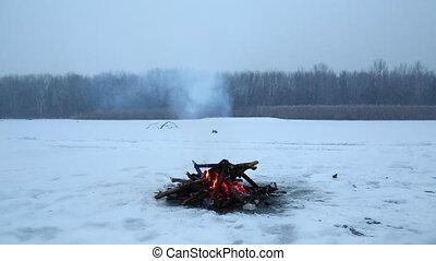 Campfire in winter - Fire in falling snow on frozen lake